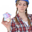 Royalty-Free Stock Photo: Craftswoman holding a little model of house made of banknotes