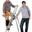 Builder stood on ladder next to apprentice — Stockfoto
