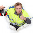 Worker giving the thumbs up to ear defenders — Stock Photo #10496474