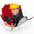 Craftsman holding a drill and breaking a paper wall — Stock Photo #10496501