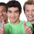 Three men giving thumbs-up sign — Stock Photo