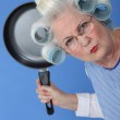 Angry old lady threatening to use frying pan — Stock Photo