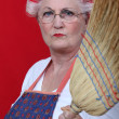 Stern elderly lady holding broom — Stock Photo #10497235