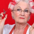 Grandmother with scissors and haircurlers — Stock Photo