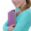 Young female student carrying folders — Stock Photo #10497392