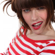 Stock Photo: Brunette wearing red and white striped shirt making grimace
