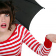 Shocked woman under an umbrella - Stock Photo