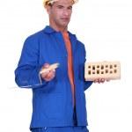 Confused mason holding brick and trowel — Stock Photo #10498477