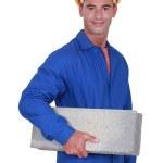 Smiling mason carrying a brick — Stock Photo #10498480