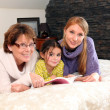 Mother, daughter and granddaughter reading book whilst laid on bed — Stock Photo