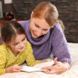 Mother teaching daughter to read — Stock Photo