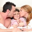 Stock Photo: Young daughter in bed with parents