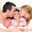 Young daughter in bed with parents - Stock Photo