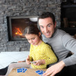 Father and daughter playing card game by fire place — Stock Photo #10499377
