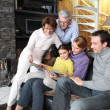 Family gathered together looking at photographs — Stock Photo
