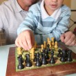 Old man playing chess with his grandson — Stock Photo #10499459
