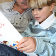 Grandfather and son reading — Stock Photo