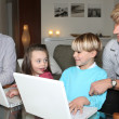 Grandparents with children and laptops — Stock Photo