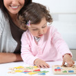 Stock Photo: Mother with daughter doing puzzle