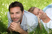 Couple lying amongst the daisies — Stock Photo