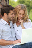 Couple of Internet users in the park — Stock Photo