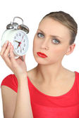 Serious looking blond woman holding alarm clock — Stock Photo