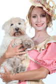 Lady in a pink and cream historical frock holding a small white dog — Stock Photo