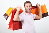 Happy man holding shopping bags — Stock Photo
