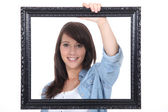 Teenage girl behind a painting frame — Stock Photo
