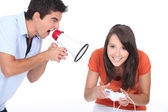 Man screaming in bullhorn while woman playing video games — Stock Photo
