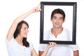 Couple stood with empty picture frame — Stock Photo