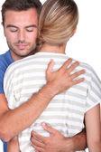 Man with closed eyes embracing a blonde — Stock Photo