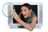 Woman with badminton racquet escaping from television — Stock Photo