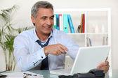 Senior businessman pointing at laptop — Stock Photo