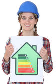 Smiling tradeswoman holding up an energy efficiency rating chart — Stock Photo