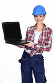 Female manual worker showing off laptop — Stock Photo