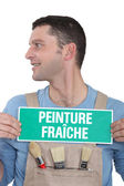 Painter with a 'Peinture Fraiche' sign — Stock Photo