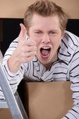Pollice in alto da un uomo con scatole di cartone — Foto Stock