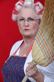 Stern elderly lady holding broom — Stock Photo