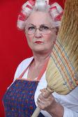 Stern elderly lady holding broom — Stock Photo