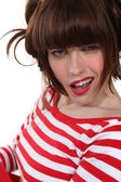 Brunette wearing red and white striped shirt making grimace — Stock Photo