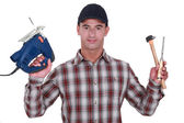 Man holding band-saw, hammer and chisel — Stock Photo
