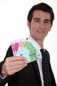 Businessman with a wad of cash — Stock Photo