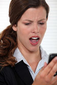 Woman staring in disbelief at her mobile phone — Stock Photo