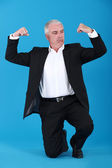 Mature businessman flewing his muscles — Stock Photo