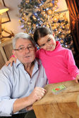 Senior man and little girl playing cards — Stock Photo