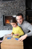 Father and daughter playing card game by fire place — Stock Photo