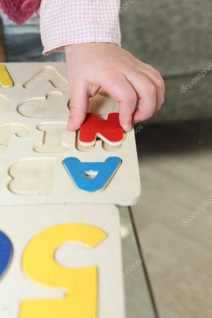 Kid playing with wooden letter puzzle — Stock Photo #10499493