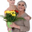 Young womgiving senior lady bunch of flowers — Stock fotografie #10500853