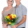 Stock Photo: Husband giving wife flowers